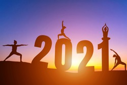 Happy New Year Numbers 2021, Silhouette woman practicing yoga early morning sunrise over the horizon background, Health and Happy new year concept.