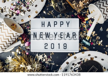 Happy new year 2019 on light box with party cup,party blower,tinsel,confetti.Fun Celebrate holiday party time table top view #1191763438