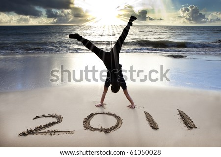 happy new year 2011 on the beach of sunrise . young man handstand and celebrate . - stock photo