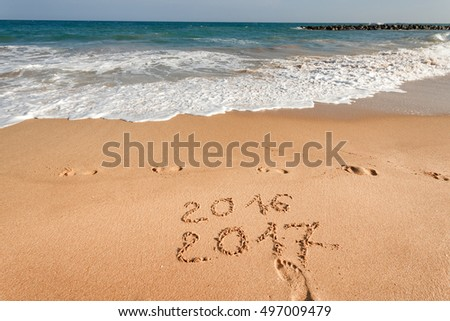happy new year 2017 replace 2016 lettering on the beach