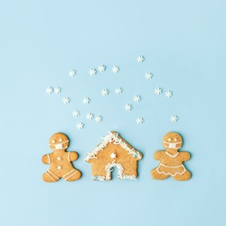 Happy New Year's set of house, gingerbread man in face mask from ginger biscuits glazed sugar icing decoration on blue background, minimal seasonal pandemic winter holiday banner, stay home