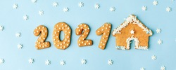 Happy New Year's set of numbers 2021 from ginger biscuits and house glazed sugar icing decoration on blue background, minimal seasonal winter holiday card, wide banner, flyer, coupon, stay home