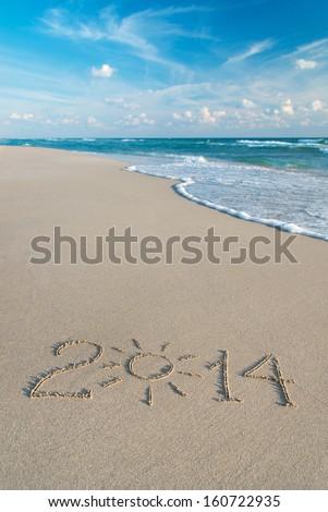 Happy New Year 2014 season concept on the sea beach with the sun rays - stock photo
