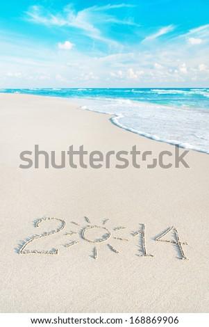 Happy New Year 2014 season concept on the sea beach with the sun rays