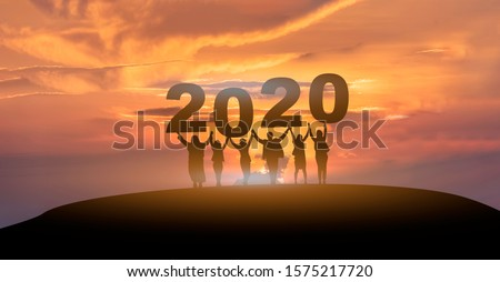 Happy new year 2020, Silhouette of 2020 letters on the mountain with business people raised arms in teamwork concept at sunrise.