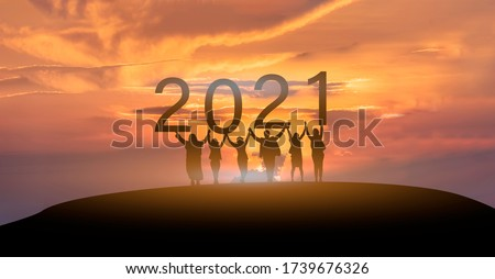 Happy new year 2021, Silhouette of 2021 letters on the mountain with business people raised arms in teamwork concept at sunrise.  商業照片 ©