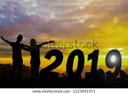 Happy new year Silhouette sunset background. They are standing beside 2019 word and see the sun set. Woman wearing a hat and man Man hugging woman.new year,2019,love,Photo Silhouette and new year.