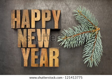 Happy New Year! - text in vintage letterpress wood type blocks on a grunge metal background with a branch of Colorado silver spruce