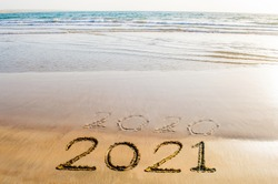 Happy New Year 2021 text on the sea beach. Abstract background photo of coming New Year 2021 and leaving year of 2020