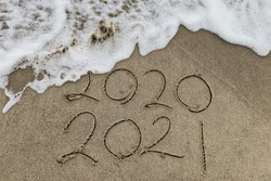 Happy New Year 2021 text on the sea beach. Handwritten inscription 2020 and 2021 on beautiful golden sand beach. Abstract background photo of coming New Year 2021 and leaving year of 2020.