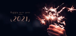 happy new year 2021 text with hand holding burning Sparkler firework blast with on a black bokeh background at night,holiday celebration event party,dark vintage tone