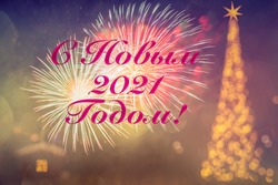Happy New Year 2021. Text written by Cyrillic in Russian. Blurred background of Christmas tree with golden lights, illumination. Fireworks. Bokeh. Greeting Postcard Russian. Wallpaper. Banner.