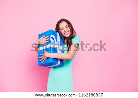 Happy New Year to me! Portrait of happy girl with long dark hair hug a gift in a blue wrapper close eyes isolated on bright pink background