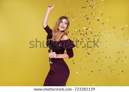 Happy New Year to you. One young and beautiful woman dancing with glass of champagne and smiling. Girl is happy about the New Year #723381139