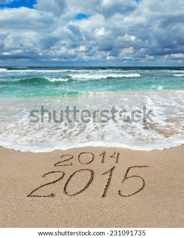 Happy New Year 2015 wash away year 2014 concept on sea sand beach