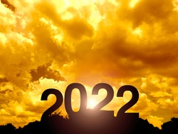 Happy New year 2022 with large silhouette letters on the mountain with beautiful sunset light, sunlight, golden sky and clouds for success concept. Welcome Merry Christmas and Happy New Year in 2022.