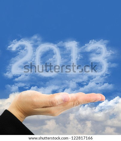 Happy New Year 2013. woman holding clouds numbers 2013