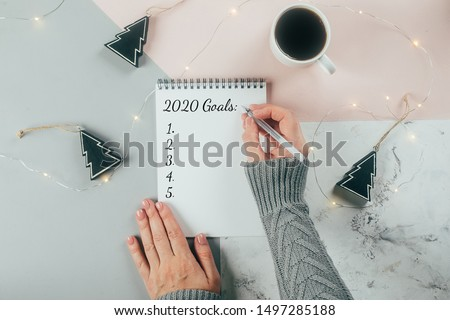 Happy New Year 2020. Woman's hand writing 2020 Goals in notebook decorated with Christmas decorations on the tricolor background. Top view, flat lay