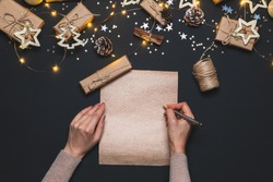 Happy New year 2021. Woman's hands writing Goals on Kraft paper decorated with Christmas Gold and silver decorations on black background. New year concept. Flat lay, top view, copy space