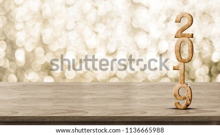 Happy New Year 2019 wood with sparkling star on brown wood table with gold bokeh background,Holiday festive celebration concept.Banner mock up for display of product or design content #1136665988