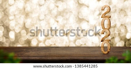 Happy New Year 2020 wood with sparkling star on brown wood table with gold bokeh background,Holiday festive celebration concept.Banner mock up for display of product or design content. #1385441285