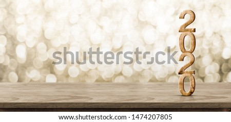 Happy New Year 2020 wood with sparkling star on brown wood table with gold bokeh background,Holiday festive celebration concept.Banner mock up for display of product or design content
