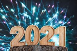 Happy New Year Wooden 2021 as text with fireworks background.