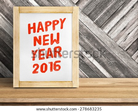 Happy New Year 2016 word on wood frame on table and diagonal plank wooden wall,Leave space beside frame to add more text.