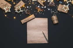 Happy New year 2021. Writing Goals on Kraft paper decorated with Christmas Gold and silver decorations on black background. New year concept. Flat lay, top view, copy space