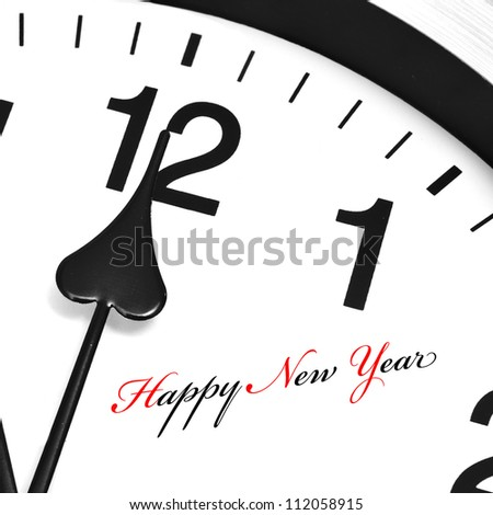 happy new year written in a clock with its hands ticking midnight