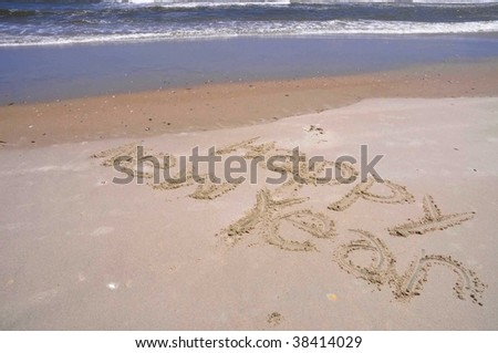 happy new year written in sand, surf in background