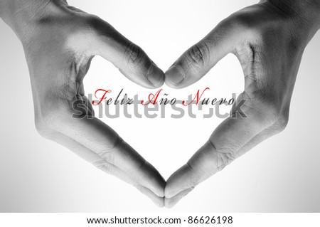 happy new year written in spanish with hands forming a heart