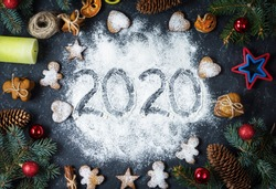 Happy New Year 2020 written on flour and Christmas Decorations Gingerbread cookies on dark stone background. Christmas, New Year greeting card