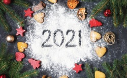 Happy New Year 2021 written on flour and Christmas Decorations Gingerbread cookies on dark stone background. New Year greeting card