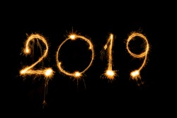 Happy new year 2019 written with sparkle fireworks on isolated black background