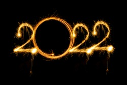 Happy new year 2022 written with sparkle fireworks on isolated black background