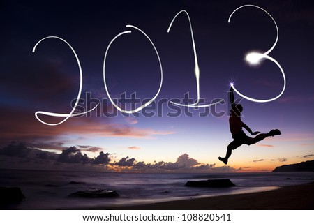 happy new year 2013. young man jumping and drawing 2013 by flashlight in the air on the beach before sunrise