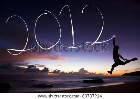 happy new year 2012. young man jumping and drawing 2012 by flashlight in the air on the beach before sunrise