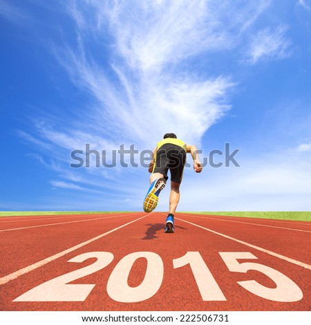 happy new year 2015 young man running on track with blue sky and cloud background