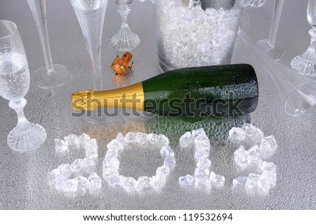 Happy New Years. 2013 spelled out with ice cubes on a wet metallic surface, surrounded by a champagne bottle, and flutes.