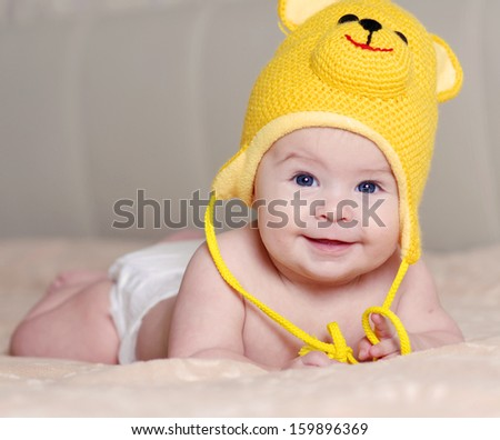 happy newborn baby in a hat with an bruin