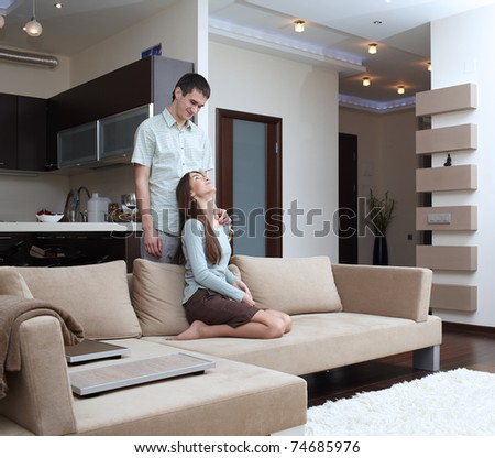 Happy newly married couple at home on sofa