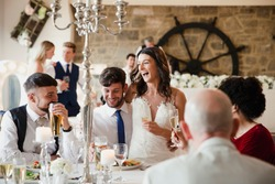 Happy, newly wed couple are socialising with guests at their wedding meal. The bride is sitting on her husband's knee and they are laughing and drinking with their friends and family.