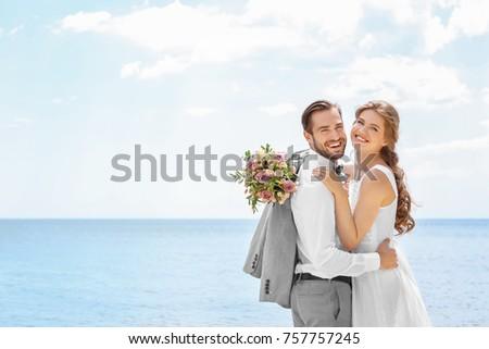 Happy newlywed couple hugging on seashore Stock photo ©