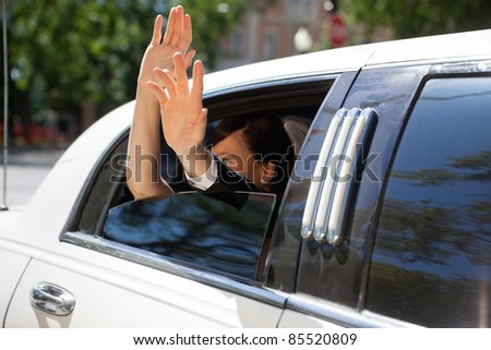 Happy newlywed couple waving out of limousine window