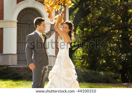 Happy newlywed young couple dancing under tree outdoors.