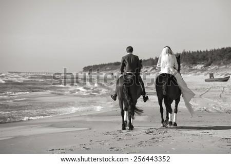 Happy newlyweds rode along the sea. Black white