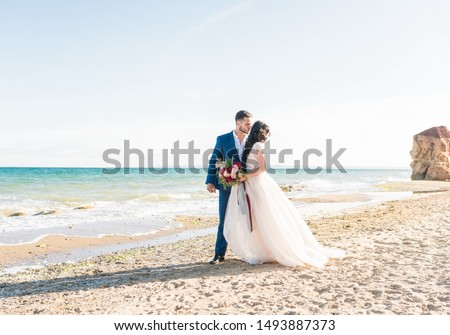 Happy newlyweds stand holding hands on the background of the blue sea. Wedding walk on a sand beach. In the background, blue sky Stock photo ©
