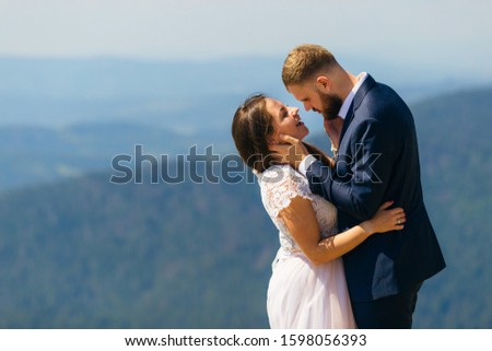 happy newlyweds standing face face to face and embracing each other. the bride smiles sincerely