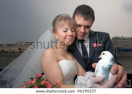 Happy newlyweds with white dove in bride's hands